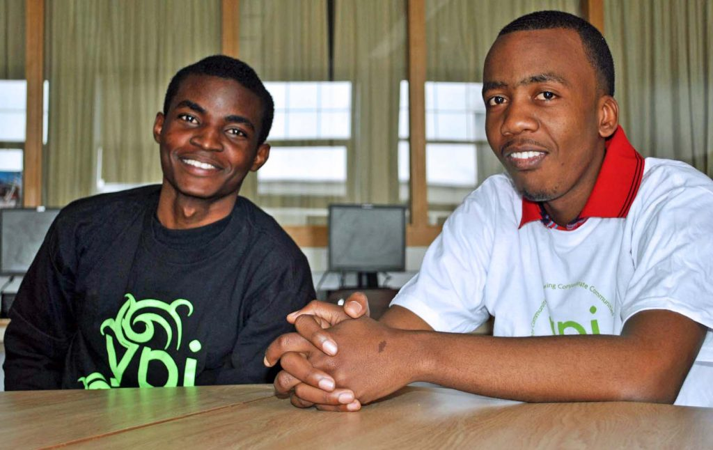 Two male students smile and look at the camera
