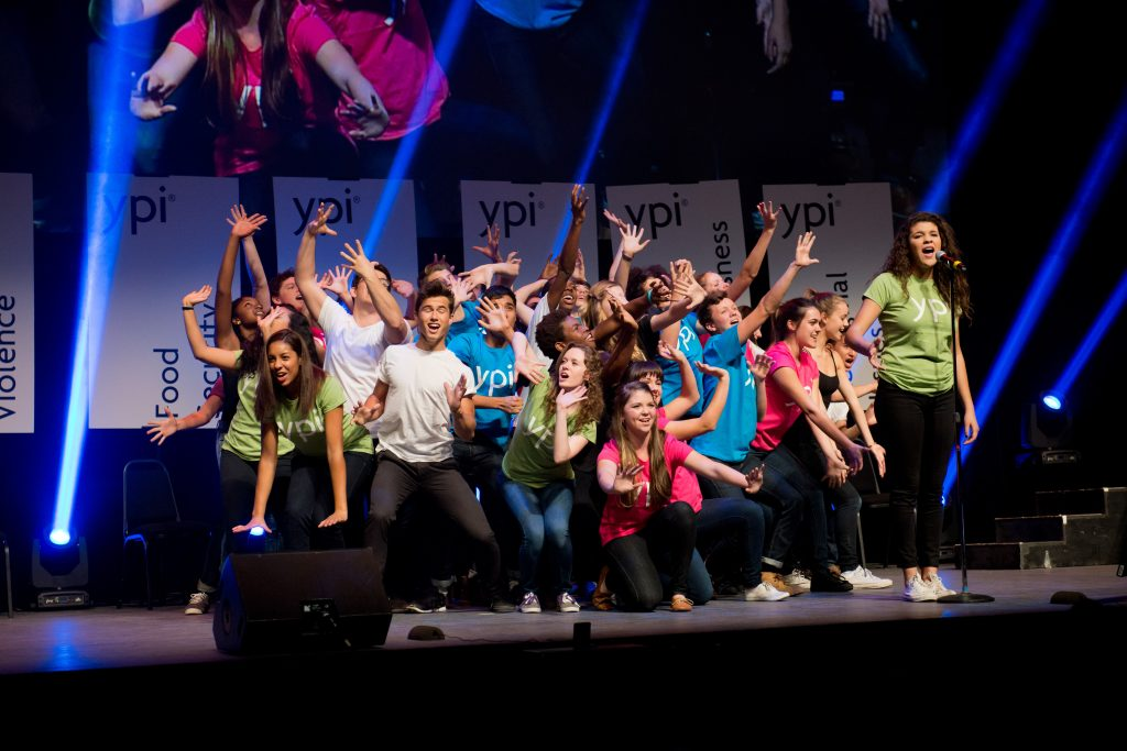 Two dozen students in colourful shirts on stage performing a musical number