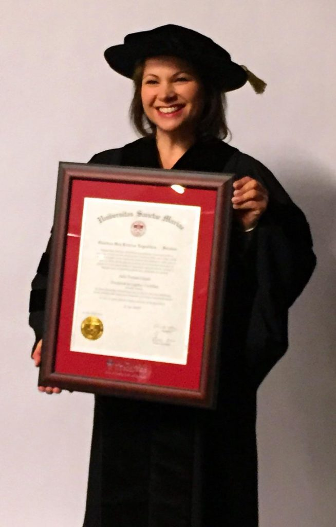 Julie Toskan holding framed copy of honourary PhD