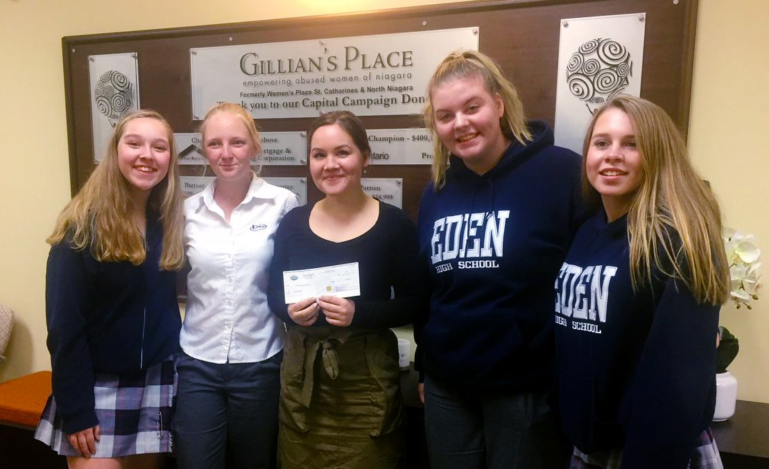 Four female students deliver a donation cheque to a charity representative.