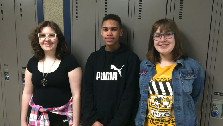 Three secondary school students from the YPI program stand in front of a row of lockers.