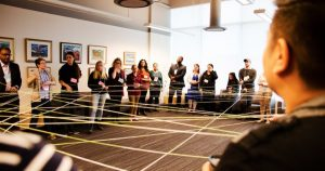 Circle of people connected to each other with strings