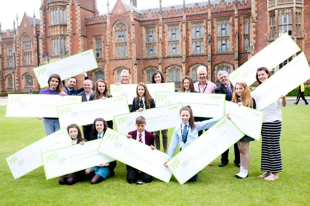 A group of students holding giant cheques on a front lawn