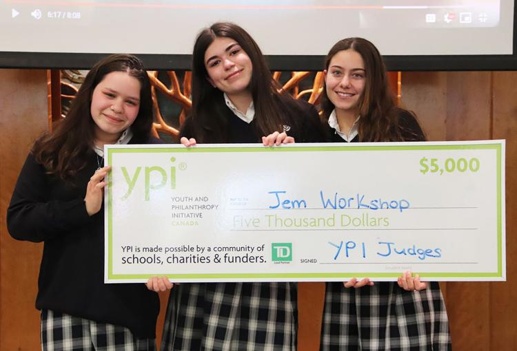 Three students hold up an oversized cheque for $5000 awarded to Jem Workshop