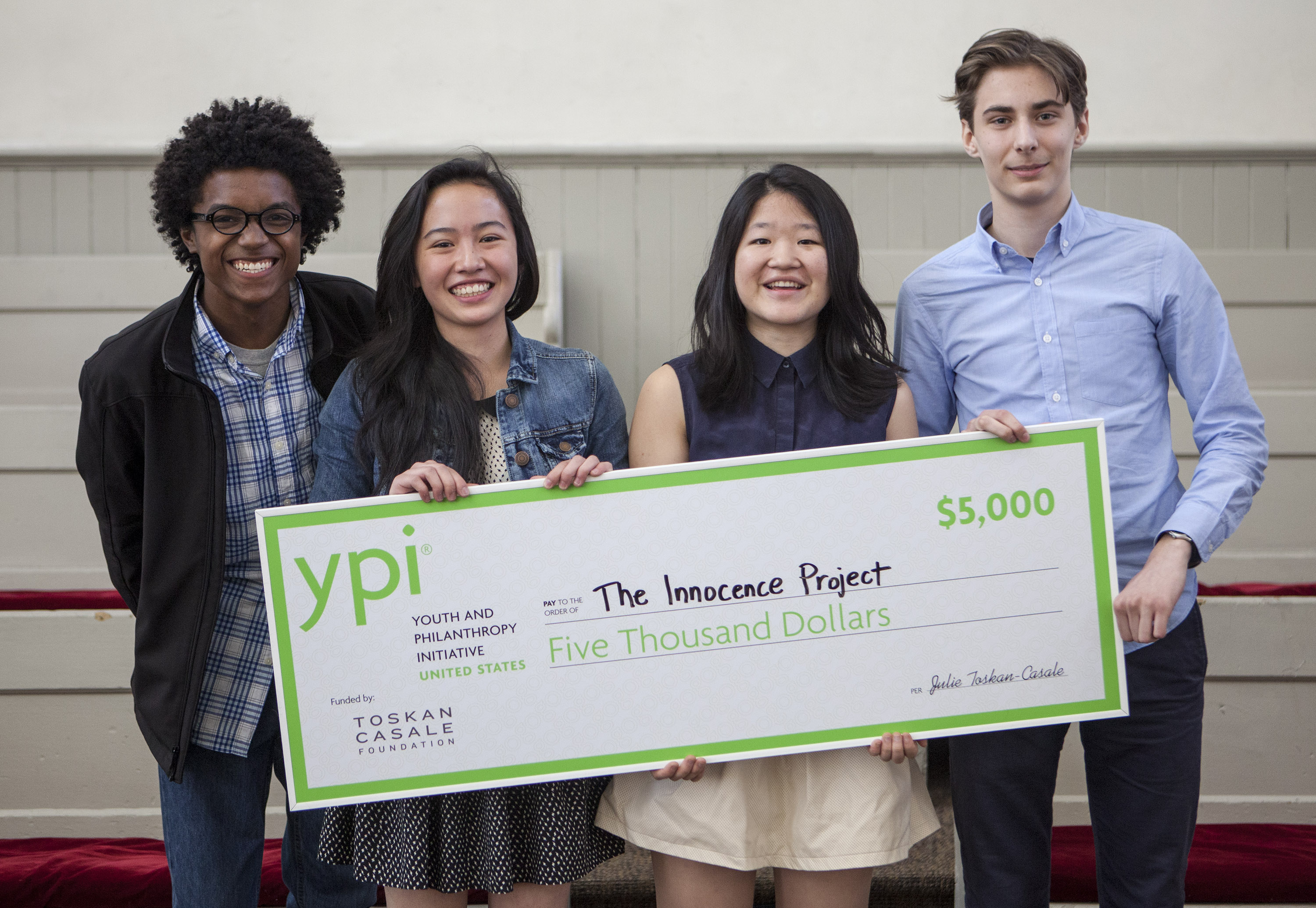 Four students hold up an oversized novelty cheque for $5000 made out to the Innocence Project.