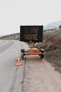"LED road sign on a highway curve that reads ""Stay Home"""